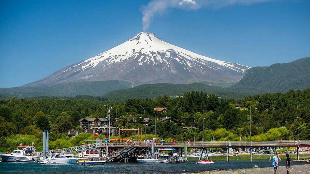 Volcan villarrica en pucon co lago, agua , lancha o yates frente de hoteles